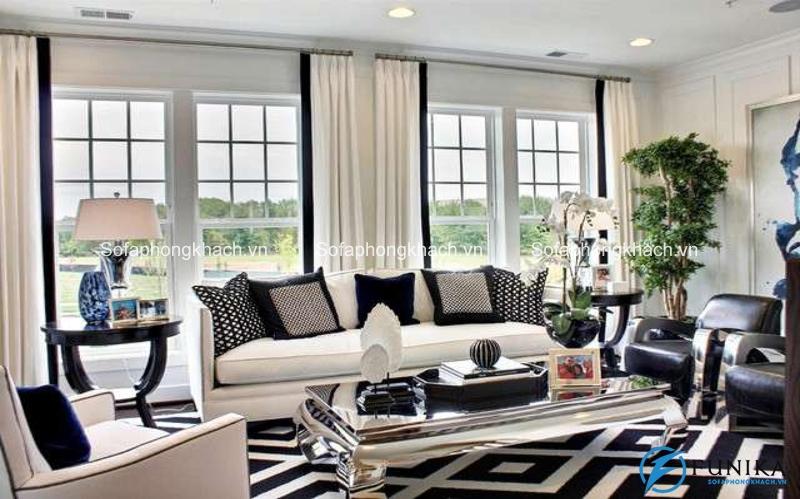Chiếc ghế sofa đi văng dài màu trắng nổi bật trên những họa tiết màu đen